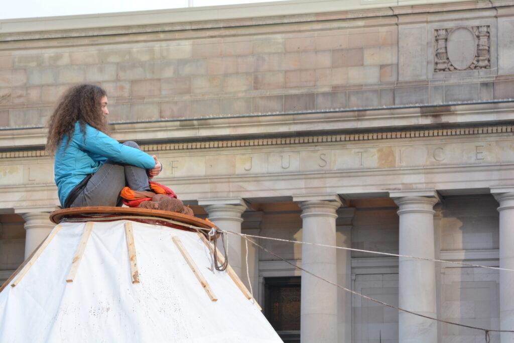 Climate justice activist atop tarpee at Washington State Capitol
