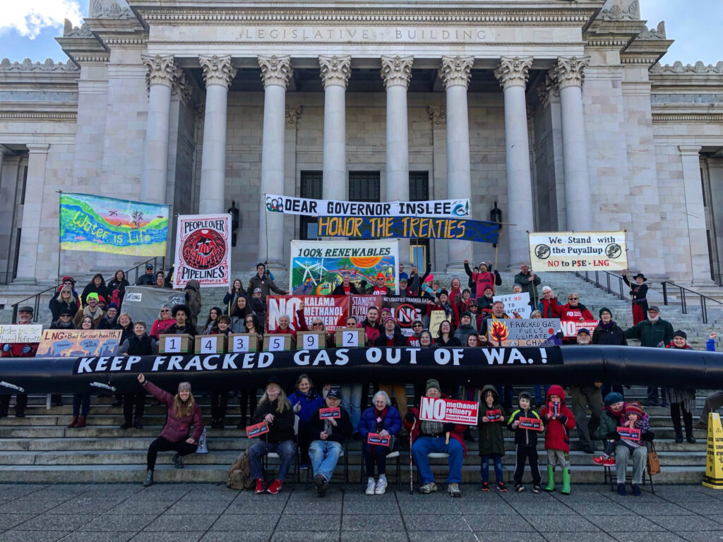 Climate activists hold banners on steps of Olympia capitol building