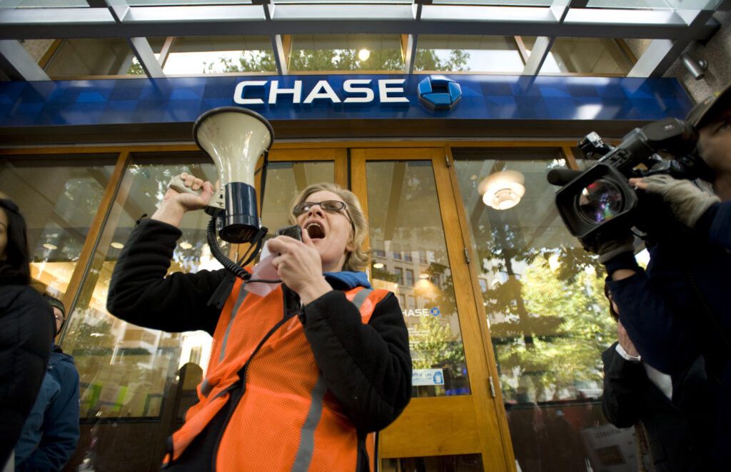Climate Justice activist with megaphone in front of Chase Bank