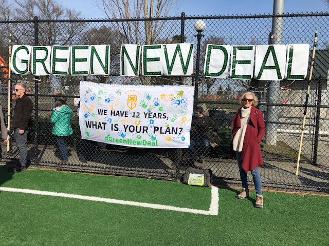 Climate justice activists unfurl a Green New Deal banner